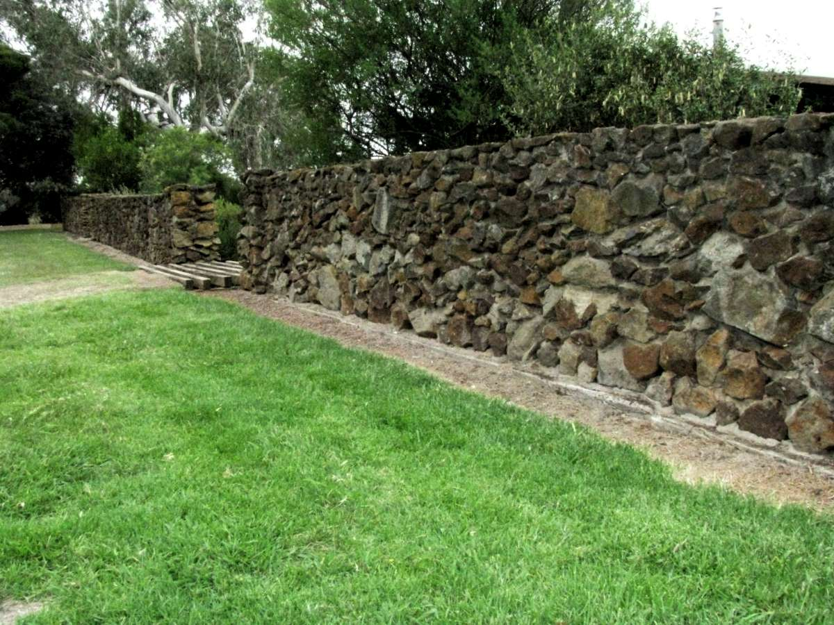 The Rock Walls Around The House Define The Garden Area.